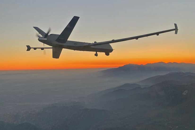 A small military plane flies above a smoky mountain range as the sun sets.