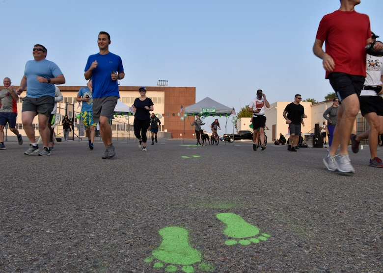Group of people spread out and running towards green feet painted on the ground.
