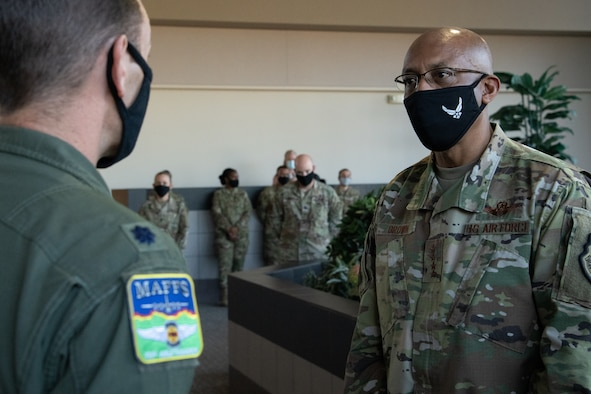 Two men converse inside a room with six onlookers in the background. Both are wearing black masks, and one is wearing an aerial firefighting patch on his flight uniform.