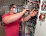 Electrician Travis Burns installs circuit breakers in an Armament Repair Shop Set panel.