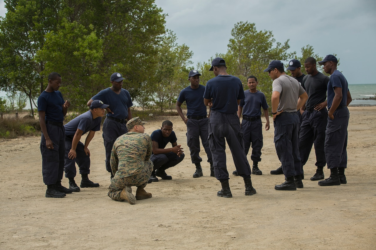 A dozen military personnel stand in a clearing for discussion.