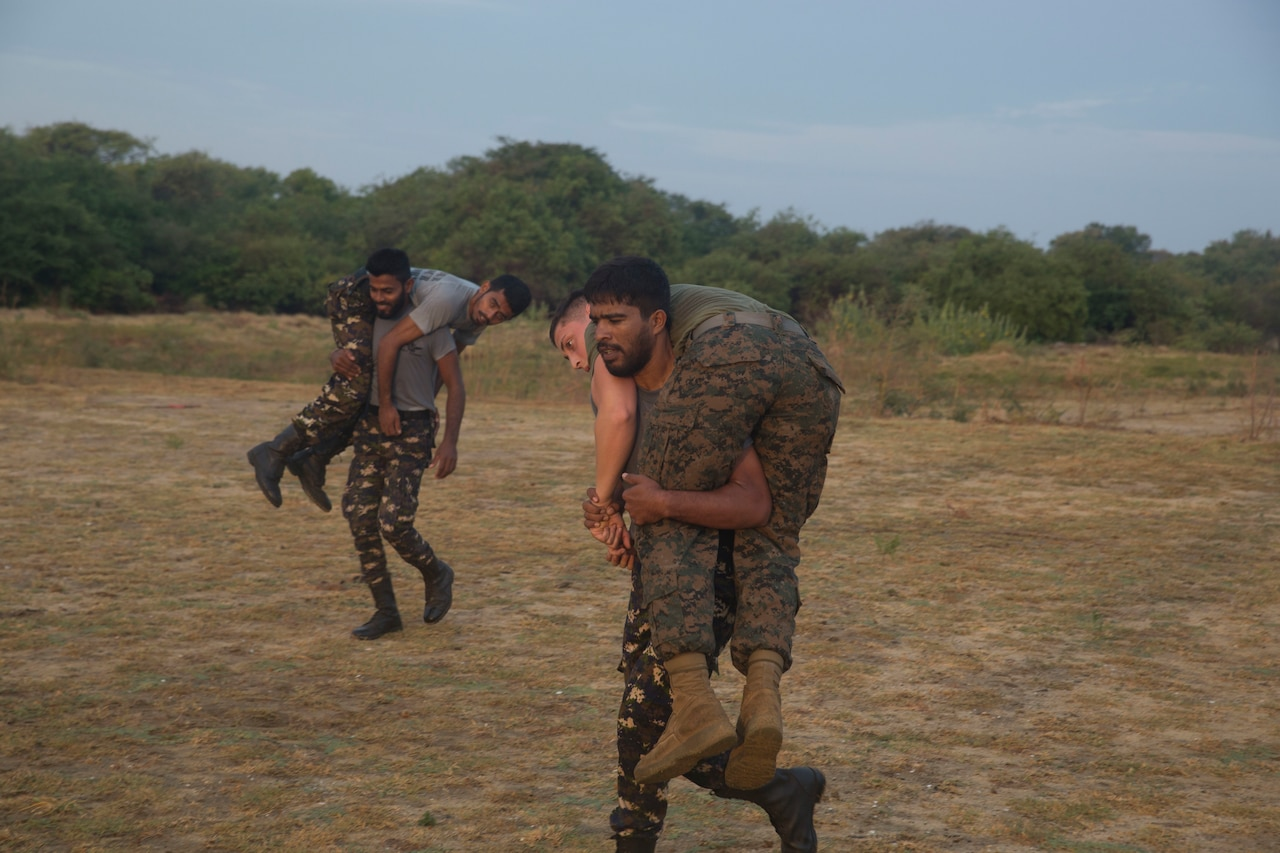 Two military personnel each carry a person over their shoulders.
