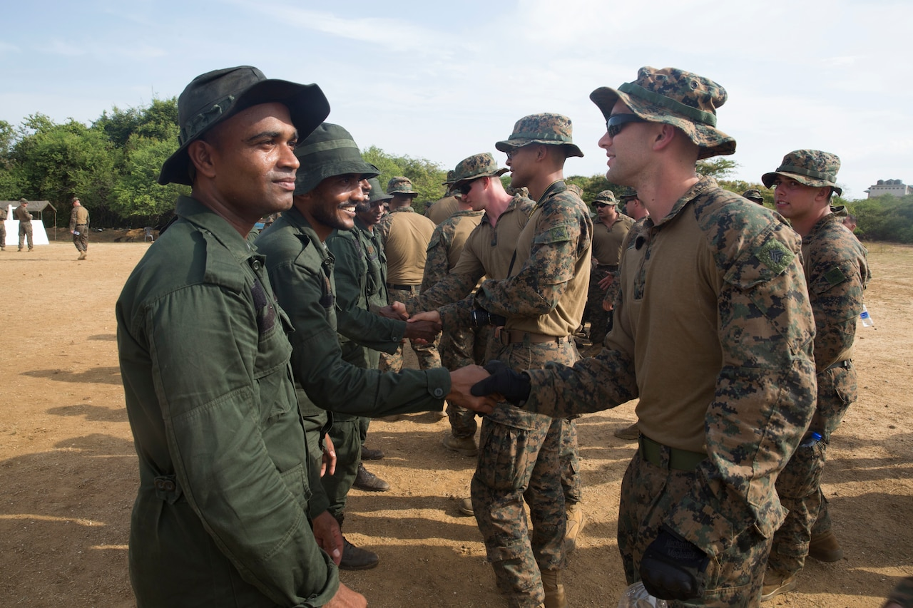 Military personnel in different uniforms shake hands with one another.