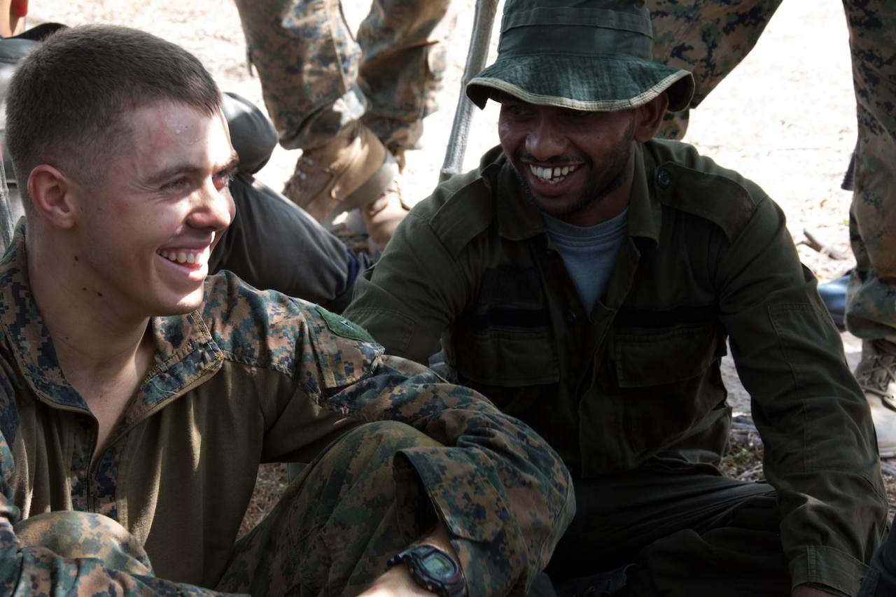 Two military personnel sit on the ground near each other.