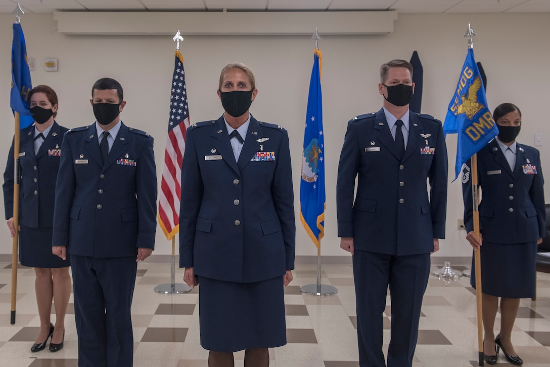 five Airmen stand during a ceremony