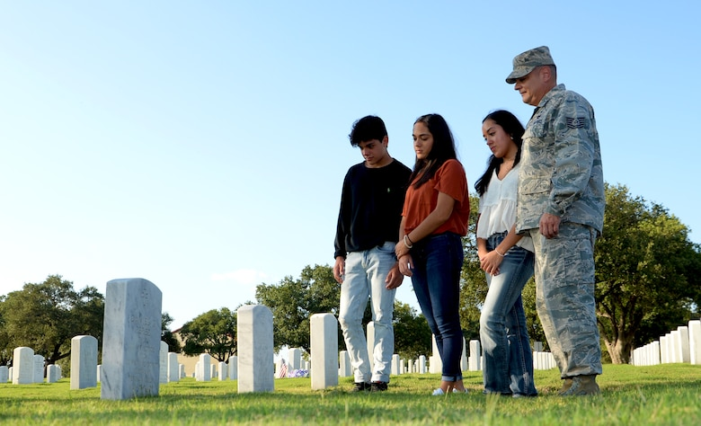 Tech. Sgt. Joseph Perez, 26th Aerial Port Squadron ramp services supervisor, visits the grave of his father Sept. 25, 2020, with his family at Fort Sam Houston Cemetery, San Antonio, Texas. (U.S. Air Force photo by Tech. Sgt. Samantha Mathison)