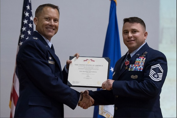Col. Casey D. Eaton, left, then-89th Airlift Wing commander, awards Senior Master Sgt. Kevin Wallace, then-89th AW public affairs chief, with a Bronze Star with Valor medal at Joint Base Andrews, Md., Aug. 15, 2017. Wallace was awarded the medal for his distinguished heroism on April 4, 2011, as a 4th Infantry Division combat photographer. Wallace, a retired senior master sergeant, shared his personal story of resilience with the Hanscom community during a virtual Suicide Prevention Month Storytellers event Sept. 22. (U.S. Air Force photo by Airman 1st Class Valentina Lopez)