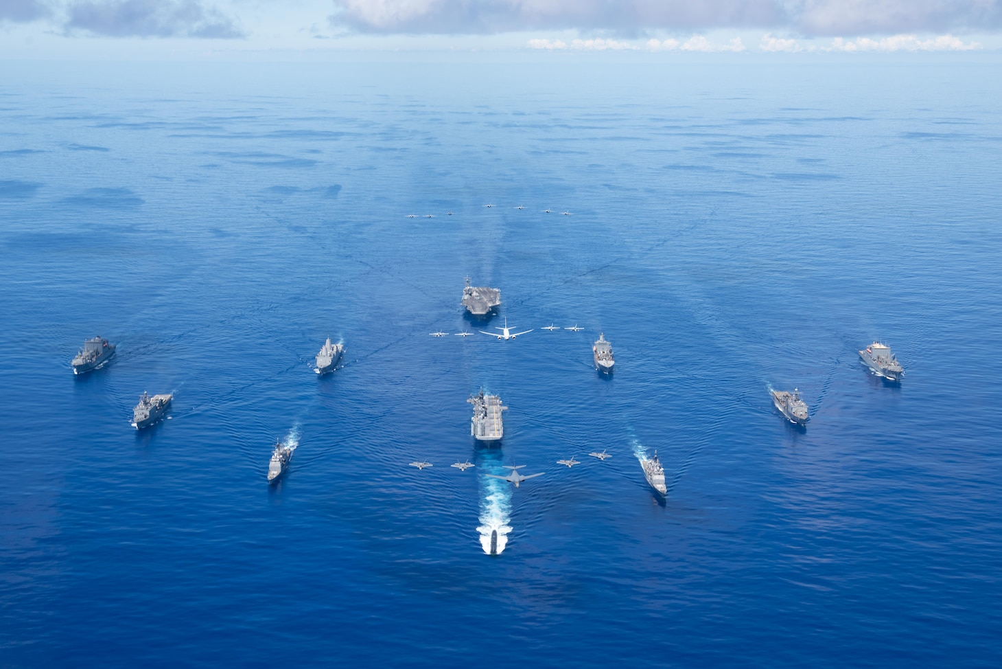 PHILIPPINE SEA (Sept. 25, 2020) From left, USNS Charles Drew (T-AKE 10), USS Comstock (LSD 45), USS Shiloh (CG 67), USS New Orleans (LPD 18), USS Chicago (SSN 721), USS America (LHA 6), USS Ronald Reagan (CVN 76), USNS John Ericsson (T-AO 194), USS Antietam (CG 54), USS Germantown (LSD 42), and USNS Sacagawea (T-AKE 2) steam in formation while E/A-18G Growlers and FA-18E Super Hornets from Carrier Air Wing (CVW) 5, a P-8 Poseidon from Commander Task Force 72,  and U.S. Air Force F-22 Raptors and  a B-1B Bomber fly over the formation in support of Valiant Shield 2020. Valiant Shield is a U.S. only, biennial field training exercise (FTX) with a focus on integration of joint training in a blue-water environment among U.S. forces. This training enables real-world proficiency in sustaining joint forces through detecting, locating, tracking and engaging units at sea, in the air, on land and in cyberspace in response to a range of mission areas. (U.S. Navy photo by Mass Communication Specialist 3rd Class Jason Tarleton)