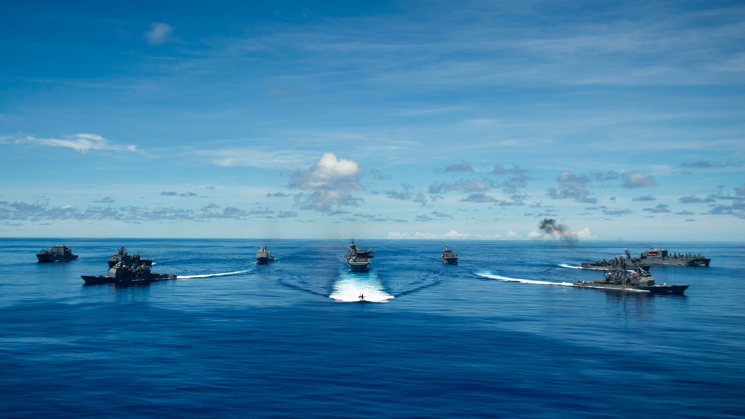 PHILIPPINE SEA (Sept. 25, 2020) From left, USNS Charles Drew (T-AKE 10), USS Comstock (LSD 45), USS Shiloh (CG 67), USS New Orleans (LPD 18), USS Chicago (SSN 721), USS America (LHA 6), USS Ronald Reagan (CVN 76), USNS John Ericsson (T-AO 194), USS Antietam (CG 54), USS Germantown (LSD 42), and USNS Sacagawea (T-AKE 2) steam in formation while E/A-18G Growlers and FA-18E Super Hornets from Carrier Air Wing (CVW) 5, a P-8 Poseidon from Commander Task Force 72, and U.S. Air Force F-22 Raptors and a B-1B Bomber fly over the formation in support of Valiant Shield 2020. Valiant Shield is a U.S. only, biennial field training exercise (FTX) with a focus on integration of joint training in a blue-water environment among U.S. forces. This training enables real-world proficiency in sustaining joint forces through detecting, locating, tracking and engaging units at sea, in the air, on land and in cyberspace in response to a range of mission areas. (U.S. Navy photo by Mass Communication Specialist 2nd Class Codie Soule)