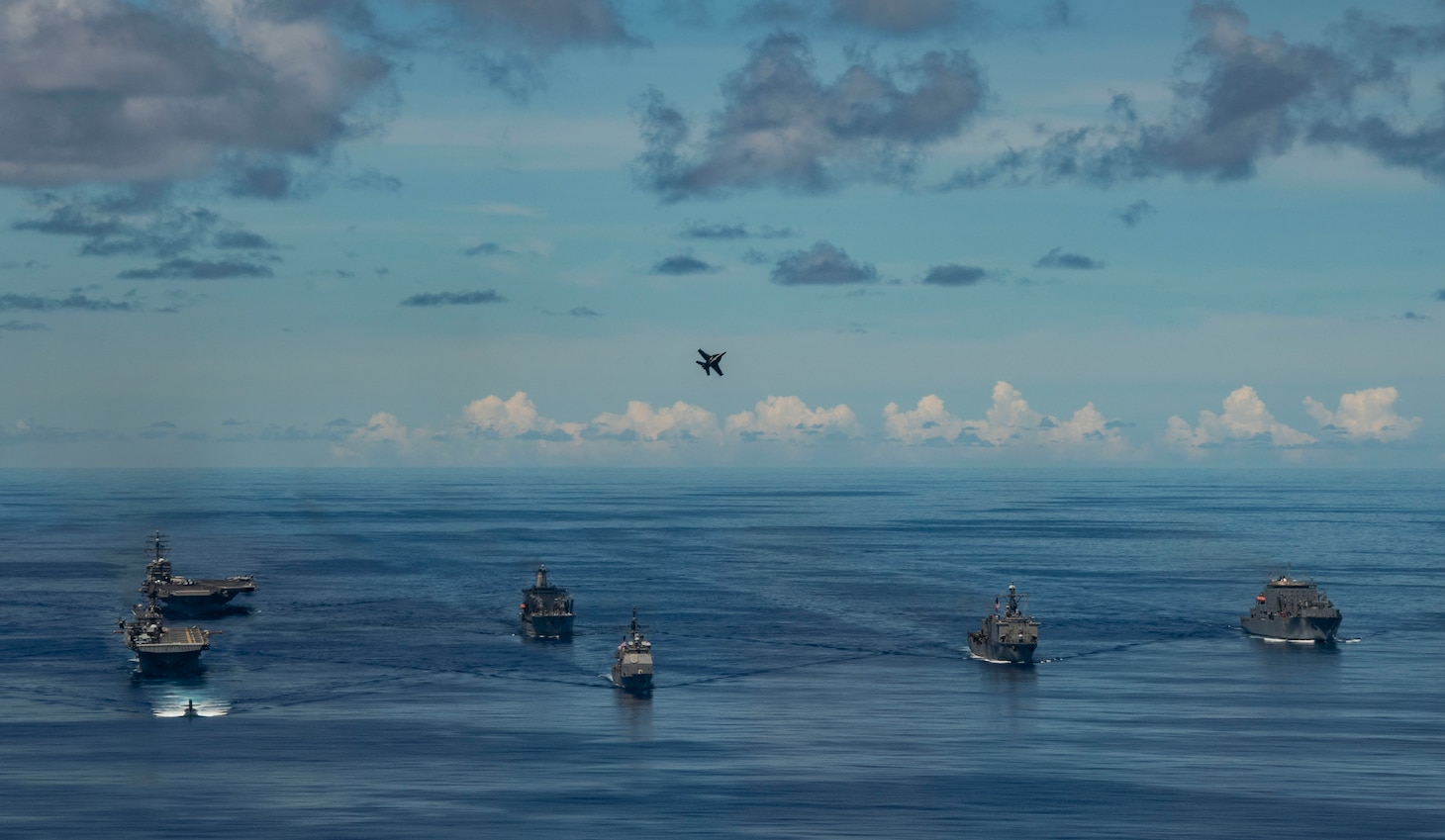 PHILIPPINE SEA (Sept. 25, 2020) USS Chicago (SSN 721), front, USS America (LHA 6), USS Ronald Reagan (CVN 76), USNS John Ericsson (T-AO 194) and USS Antietam (CG 54) steam in formation while an F/A-18E Super Hornet, attached to the Eagles of Strike Fighter Squadron (VFA) 115, flies over the formation in support of Valiant Shield 2020. Valiant Shield is a U.S. only, biennial field training exercise (FTX) with a focus on integration of joint training in a blue-water environment among U.S. forces. This training enables real-world proficiency in sustaining joint forces through detecting, locating, tracking and engaging units at sea, in the air, on land and in cyberspace in response to a range of mission areas. (U.S. Navy photo by Mass Communication Specialist 2nd Class Erica Bechard)