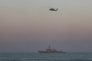 An MH-60R Seahawk helicopter flies over the guided-missile destroyer USS Winston S. Churchill (DDG 81) during the joint air operations in support of maritime surface warfare (AOMSW) exercise in the Arabian Gulf, Sept. 24. Combined integration operations between joint U.S. forces are regularly held to maintain interoperability and the capability to counter threats posed in the maritime domain, ensuring freedom of navigation and free flow of commerce throughout the region's heavily trafficked waterways. (U.S Army photo by Spc. William Gore)