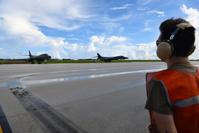 A maintainer assigned to the 34th Expeditionary Bomb Squadron, Ellsworth Air Force Base, S.D., prepares to marshal a B-1B Lancer for take-off during Exercise Valiant Shield at Andersen AFB, Guam, Sept. 18, 2020. Valiant Shield is a series of military exercises that promote integration and interoperability among joint forces. Each successive exercise builds on lessons learned from the previous training to validate and enhance complementary capabilities and develop new tactics, techniques and procedures. (U.S. Air Force photo by Staff Sgt. Nicolas Z. Erwin)