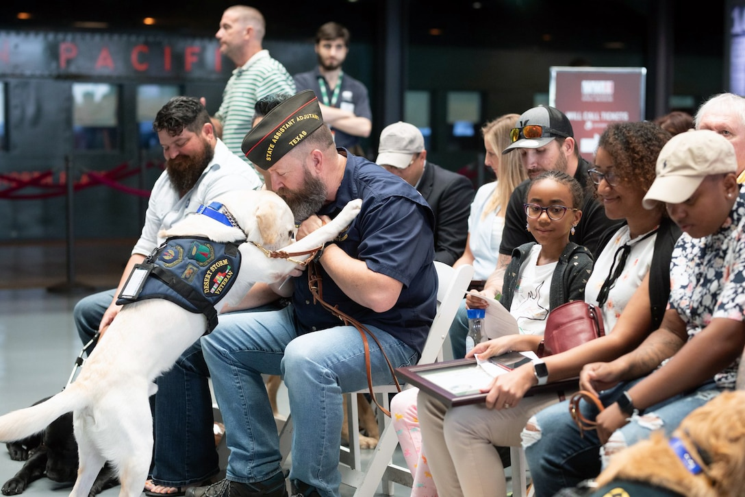 "Andrew Camplen, on his graduation day when he received Sebestian, his service dog at the National WWII Museum, New Orleans, LA, Aug. 24, 2019. ""I was sitting in a chair waiting on my dog to be delivered. And I have to say that Monday, my heart was pounding, and the adrenaline rush, and then Sebastian was walked into the room by his trainer. Camplen is now the Director of Client Services for the United States Veterans Service Dogs, which was created for and dedicated to helping veterans return to a new ""Normal"" by training and placing quality service dogs with veterans."