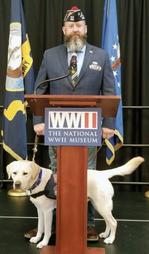 """Andrew Camplen, Director of Client Services for the United States Veterans Service Dogs, provides the commencement speech while his service dog, Sebastian, stands-by at the USVSD, Dec. 2019 graduation at the National WWII Museum, New Orleans, Louisiana. The USVSD was created for and dedicated to helping veterans return to a new """"Normal"""" by training and placing quality service dogs with veterans."""