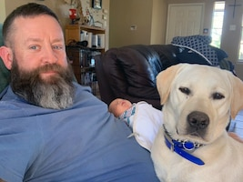 """Veteran Andrew Camplen, at home, welcomes his newborn baby boy, with his service dog, Sebastian, who never leaves his side, winter 2019. After separation from the Air Force and working for the San Antonio police department, Camplen realized that he needed a service dog. Camplen is now the Director of Client Services for the United States Veterans Service Dogs, which was created for and dedicated to helping veterans return to a new """"Normal"""" by training and placing quality service dogs with veterans."""