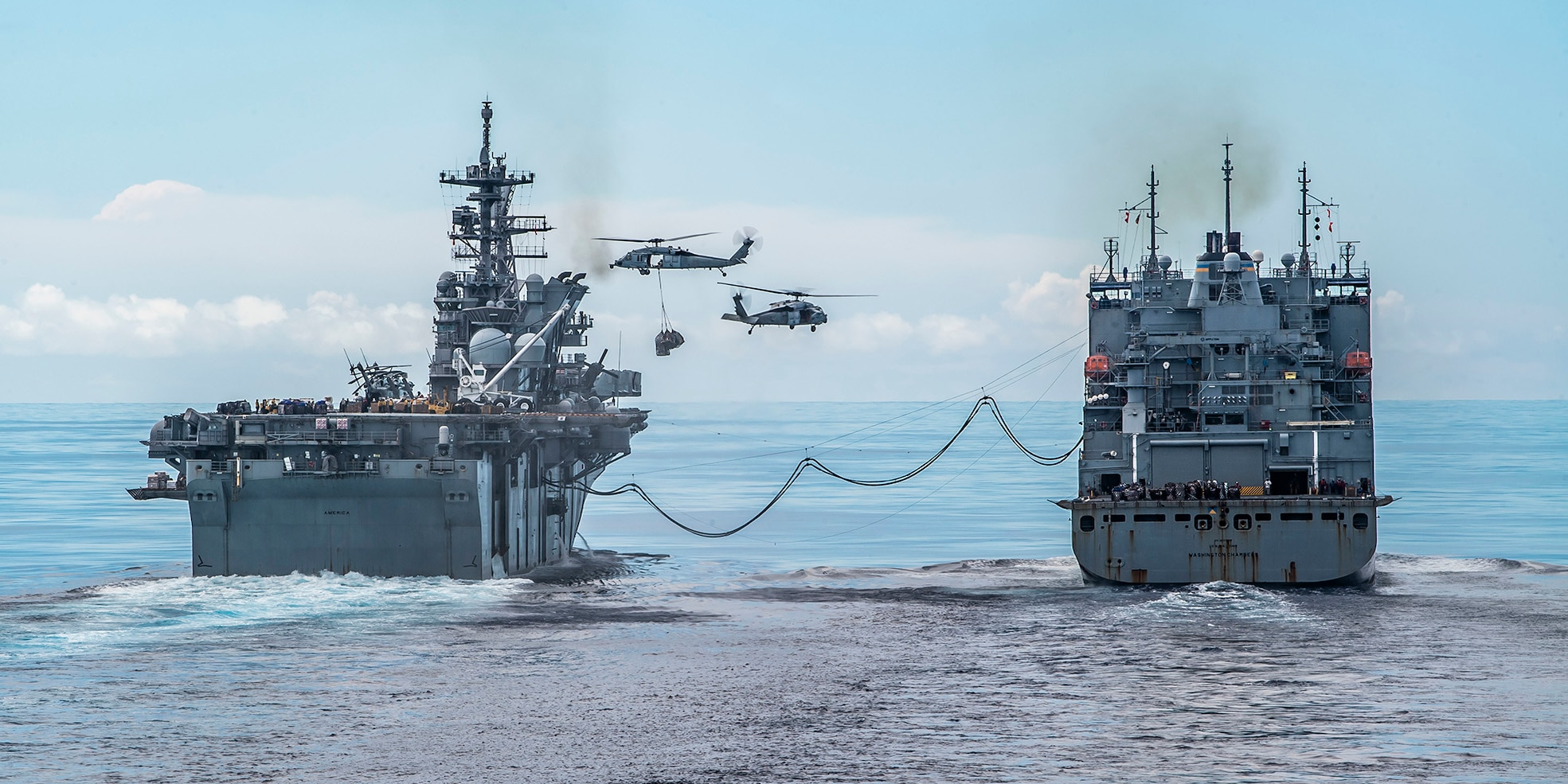 The amphibious assault ship USS America (LHA 6), left, conducts a replenishment-at-sea with the dry cargo and ammunition ship USNS Washington Chambers (T-AKE 11).
