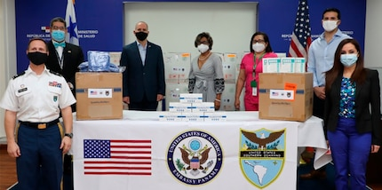 People in mask pose for a photo around a table with donated personal protection equipment.