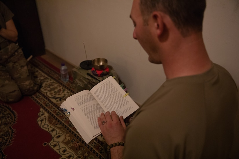 Warrant Officer 1 Erik Hodge reads from a meditation book during the Buddhist group meditation session on August 24, 2020, at Camp Buehring, Kuwait's Spiritual Life Center. The mobility officer for the 82nd Airborne Division based out of Fort Bragg, Hodge has been training to lead the meditation classes from Capt. Andrew Dahlstrom once Dahlstrom leaves theater.