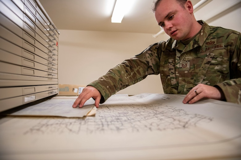 Tech. Sgt. Kevin Cuningham, 9th Civil Engineer Squadron noncommissioned officer in charge of Execution Support, pulls a map out of a cabinet on Beale Air Force Base.