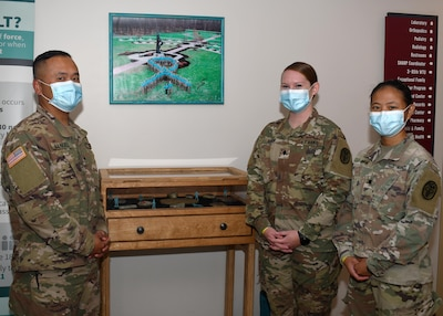 (From left to right) Staff Sgt. Dennis Manuel, primary care noncommissioned officer; Spc. Marissa Kirian, NCO in charge of OB/GYN; and Spc. Kelly Pham, laboratory medical specialist, stand in front of the Fort Drum Medical Activity's Sexual Harassment and Assault Response and Prevention display at the Guthrie Army Medical Home on Fort Drum, N.Y. Sept. 23, 2020.  Manuel, Kirian and Kelly recently received training as Sexual Assault Medical Forensic Examiner (SAMFE) assists.  Under the new pilot program, the volunteer Soldiers will now be on call to assist with medical exams, collect forensic evidence, and support victims during sexual assault forensic exams (SAFE).
