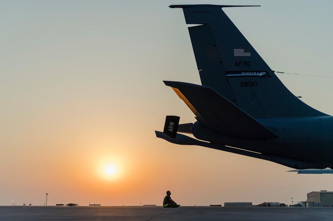 An airman sits behind an aircraft.