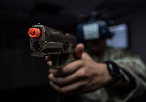 A man in a military uniform holds an orange-tipped virtual reality gun and headset in a dark room