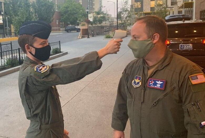 A person checks another person's temperature