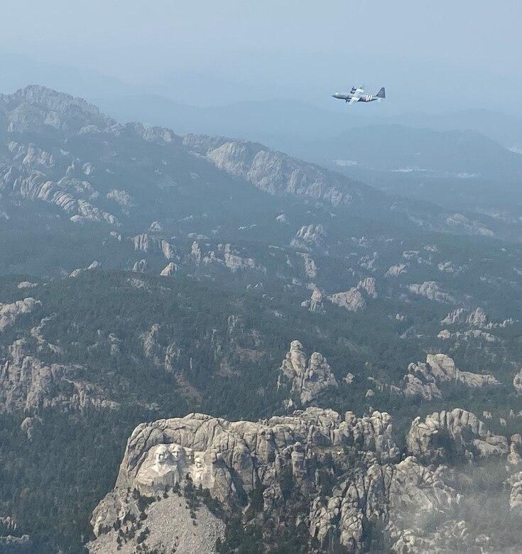An aircraft flies through the mountains