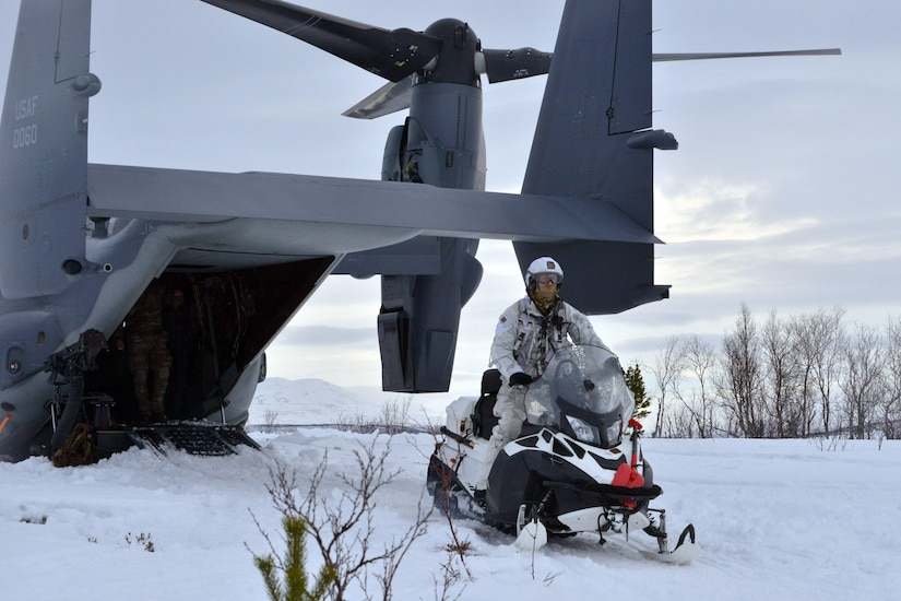 A man rides a snowmobile. A helicopter is behind him.