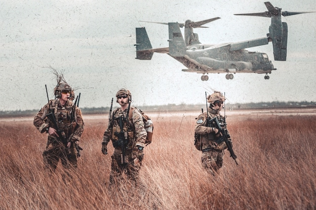 Three service members with weapons walk through a field as an aircraft hovers behind them.