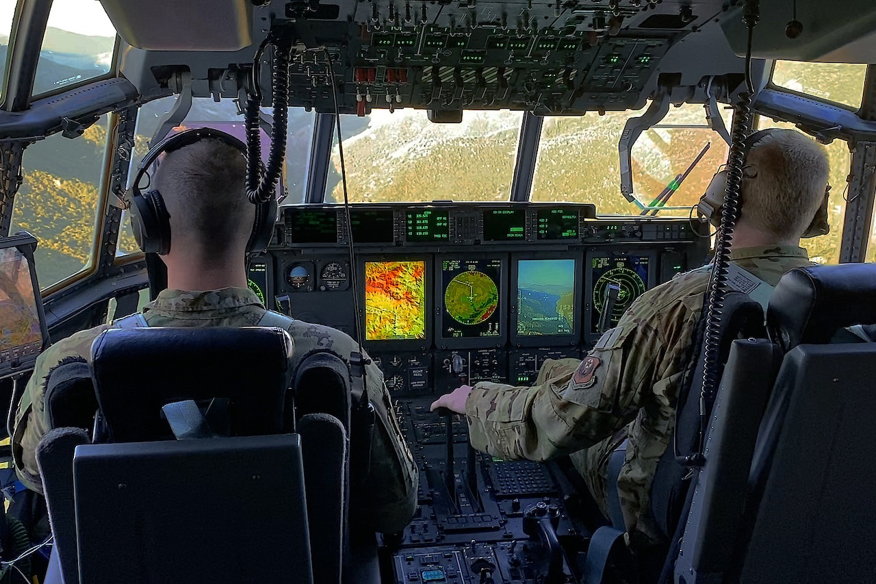 Inside a cockpit, two pilots view the control panel as they fly over rugged terrain.