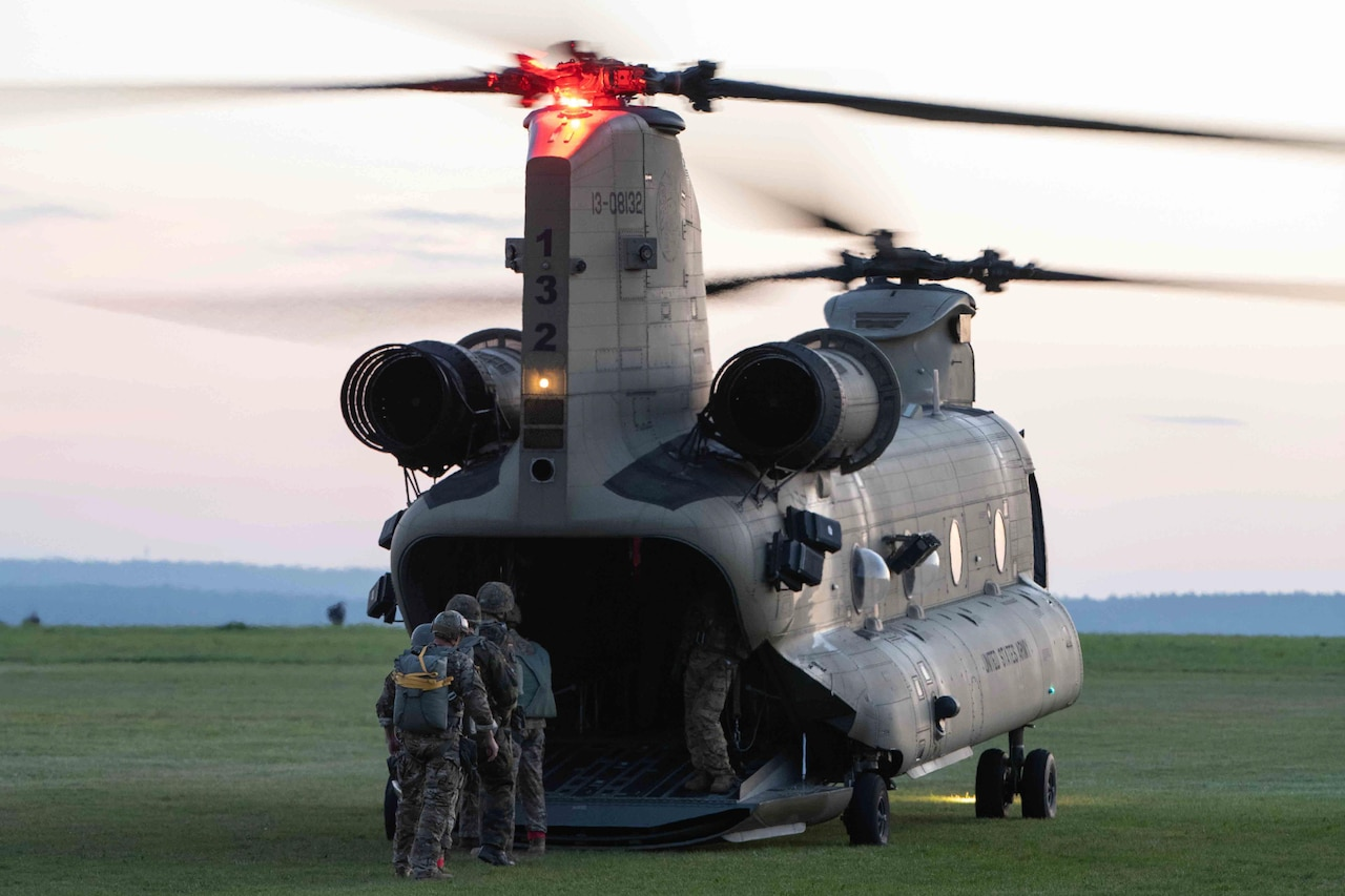 Three service members prepare to board a helicopter.