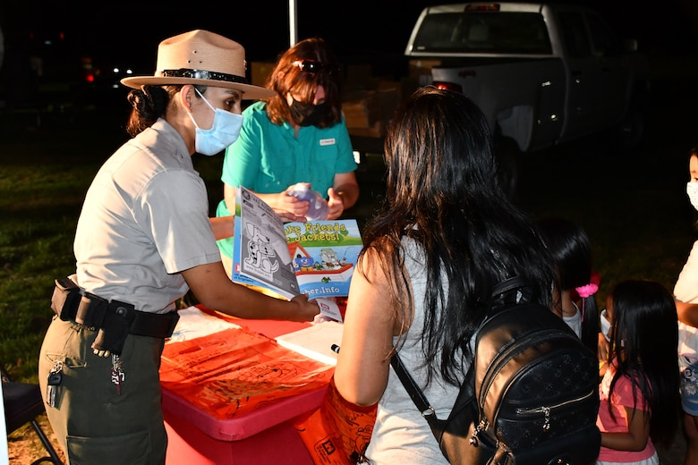 LA District Park Rangers Annel Montsalvo, left, and Linda C. Babcock, hand out information to a family participating in Los Angeles County's Overnight Family Camping and Fishing Sept. 26 at Whittier Narrows Recreation Area in Montebello, California. Montsalvo and other LA District park rangers used the event as an opportunity to educate members of the public on topics such as water safety, environmental stewardship and flood preparedness as part of National Public Lands Day.