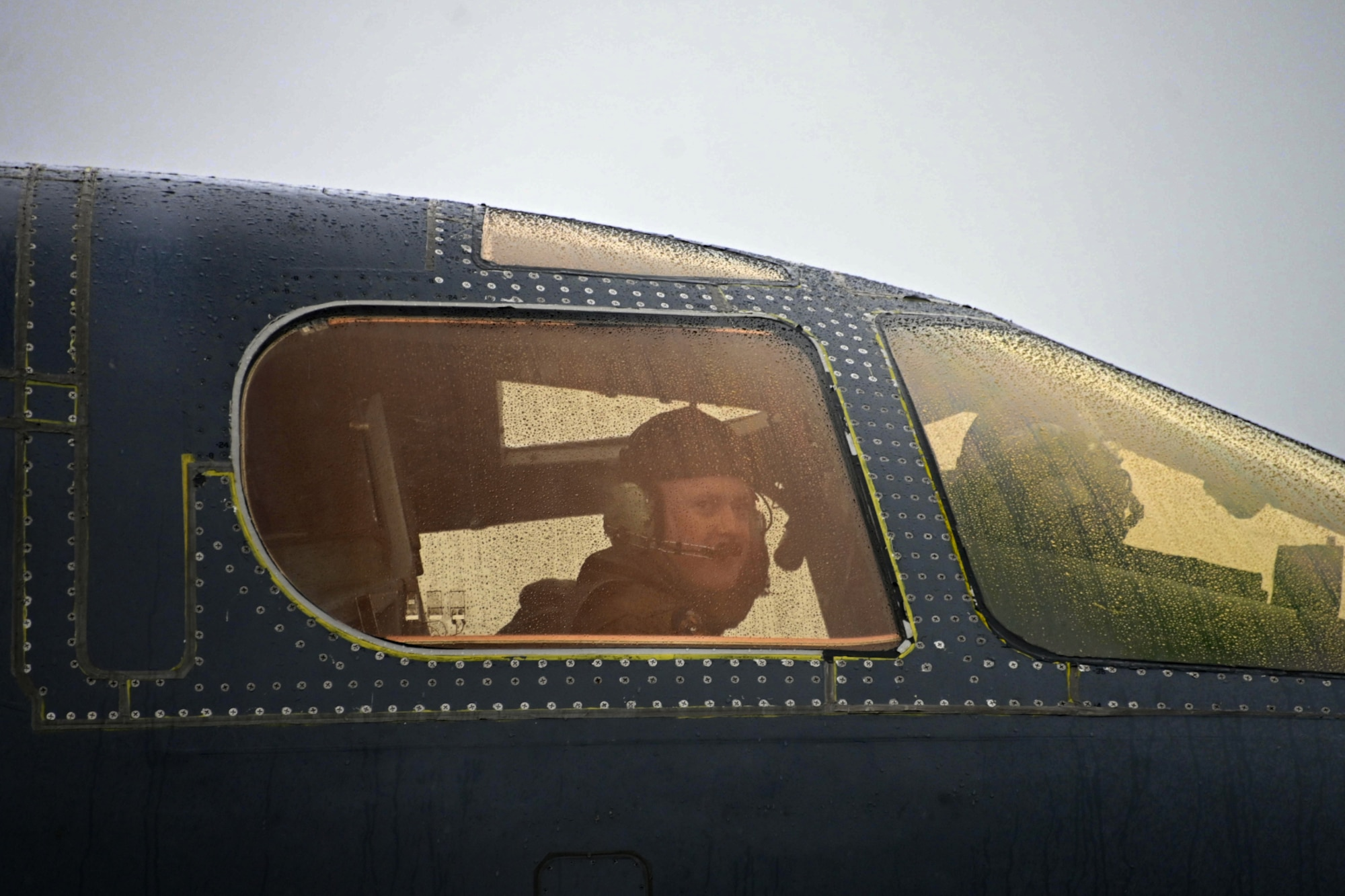 Photo of pilot looking out of the cockpit of a B-1 Lancer.