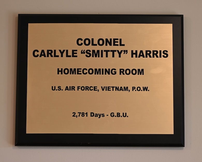 "A plaque with Ret. Col. Carlyle ""Smitty"" Harris' name is placed above a room dedicated to Harris. Harris and other POWs would use a tap code to tap the acronym ""G.B.U."", which stands for ""God Bless You"". (U.S. Air Force photo by Airman 1st Class Davis Donaldson)"