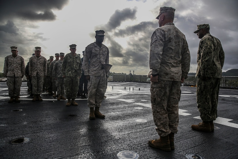 A Marine stands at attention on a ship's deck, facing two Marine Corps officers and with a crowd of fellow Marines behind him.