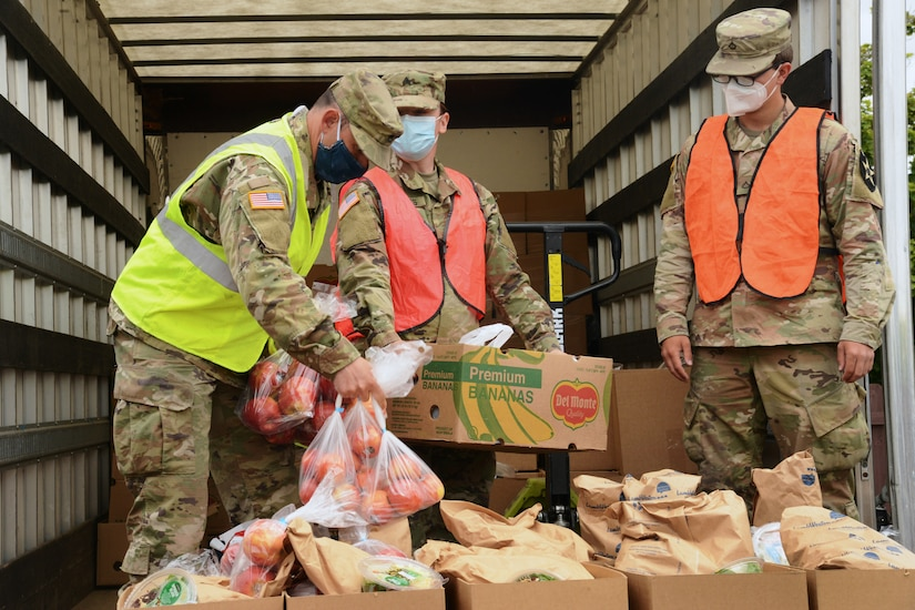 National Guard members sort food on a truck.