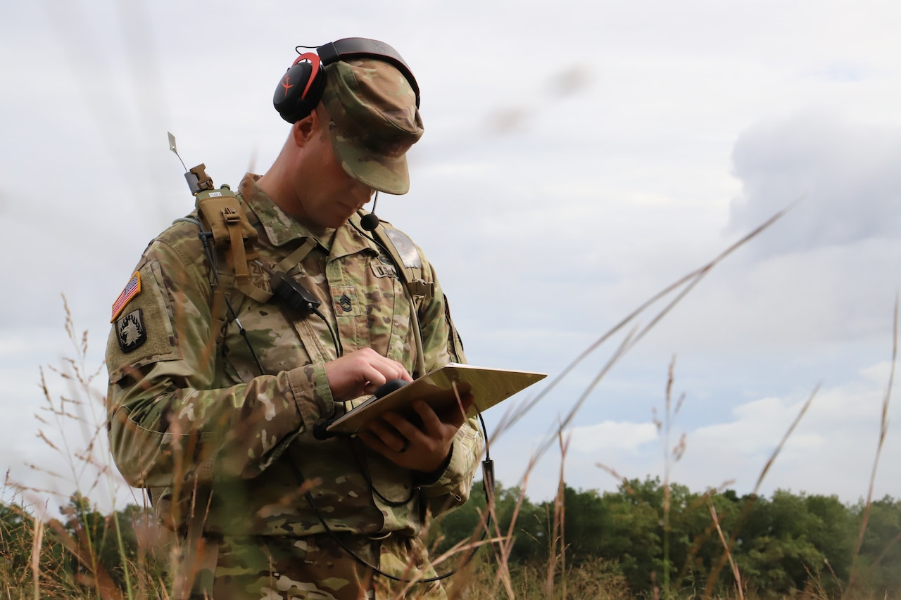 A soldier uses network gear in the field.