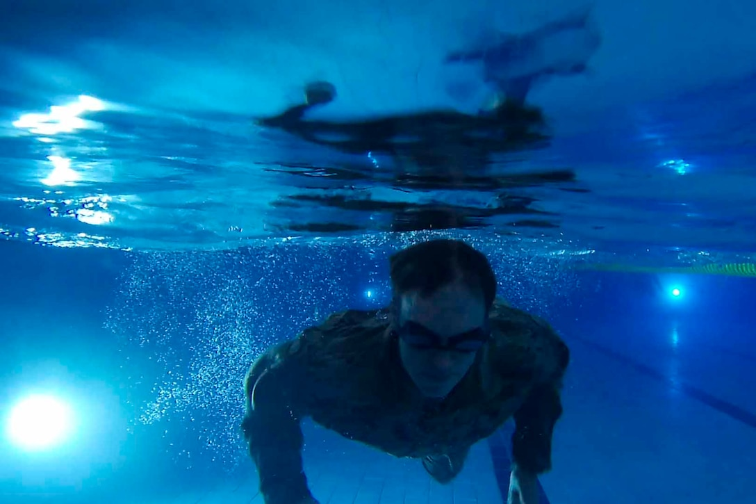 A soldier in uniform swims in a pool.