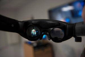A pair of augmented reality goggles show an animated robot floating above a desktop in the newly-opened innovation lab at Yokota Air Base, Japan, Sept. 25, 2020. Although AR has been marketed through the lens of gaming and entertainment, its practical application in the workplace is increasing every day. (U.S. Air Force photo by Staff Sgt. Taylor A. Workman)