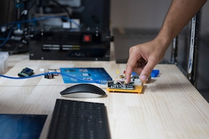 Master Sgt. Kenneth Martin, 753rd Special Operations Aircraft Maintenance Squadron production superintendent, reaches for an Arduino in the the Dojo, a newly-opened innovation lab at Yokota Air Base, Japan, Sept. 25, 2020. An Arduino allows users to prototype or create electronic systems and is just one of the many tools available in the innovation lab. (U.S. Air Force photo by Staff Sgt. Taylor A. Workman)