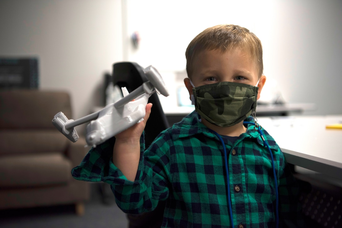 Finley Wilson, son of Master Sgt. Daniel Wilson, 5th Air Force intelligence, surveillance, reconnaissance and cyber effects operations superintendent, plays with a 3D print of a CV-22 Osprey in the newly-opened innovation lab at Yokota Air Base, Japan, Sept. 25, 2020. The lab is a dedicated space filled with tools and resources to collaboratively solve problems. (U.S. Air Force photo by Staff Sgt. Taylor A. Workman)