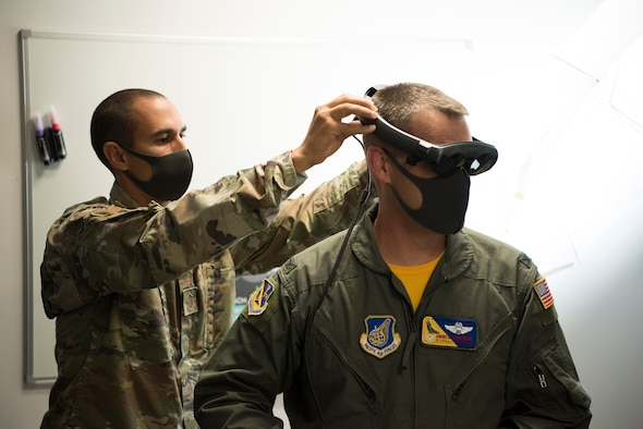 Master Sgt. Kenneth Martin, 753rd Special Operations Aircraft Maintenance Squadron production superintendent puts augmented reality goggles on Col. Andrew Campbell, 374th Airlift Wing commander, in the newly-opened innovation lab at Yokota Air Base, Japan, Sept. 25, 2020. Although newly created and opened, 'The Dojo' is stocked with top-tier technology such as AR, 3D printers, prototyping software, and reverse-engineering tools. (U.S. Air Force photo by Staff Sgt. Taylor A. Workman)