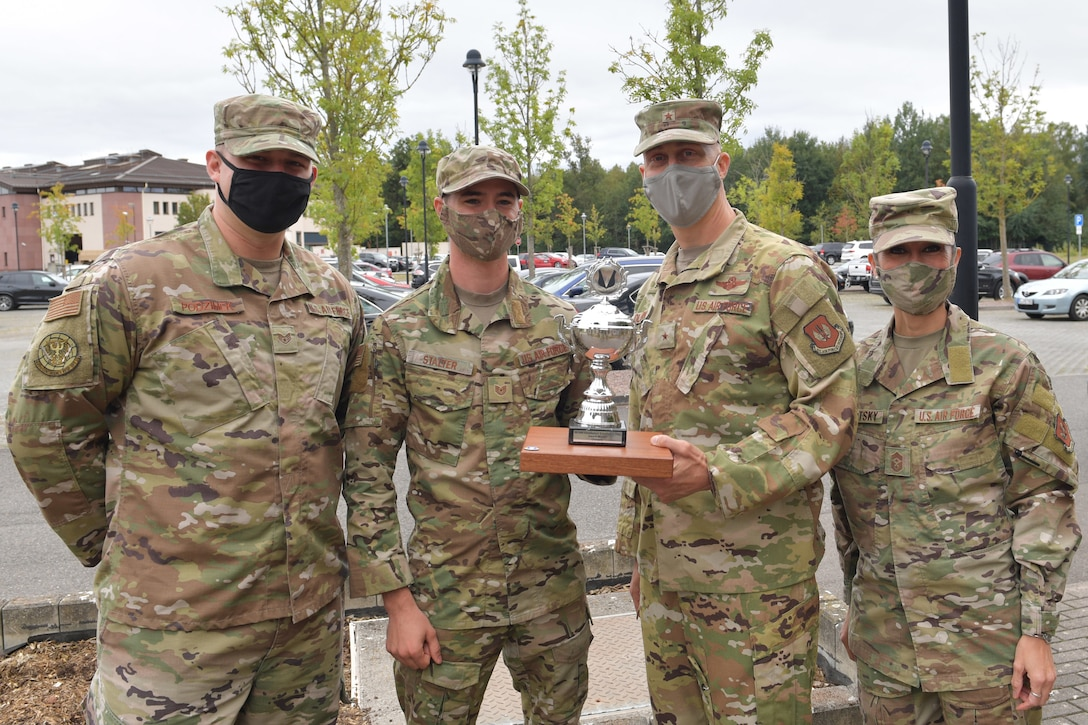 Four Airmen standing with a trophy.