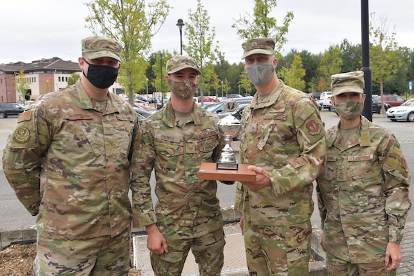 Two Airmen and a civilian posing for a photo with a trophy.