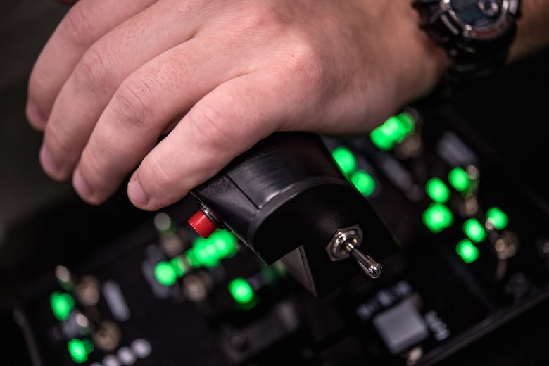 Photo of a hand on a flight simulator control console