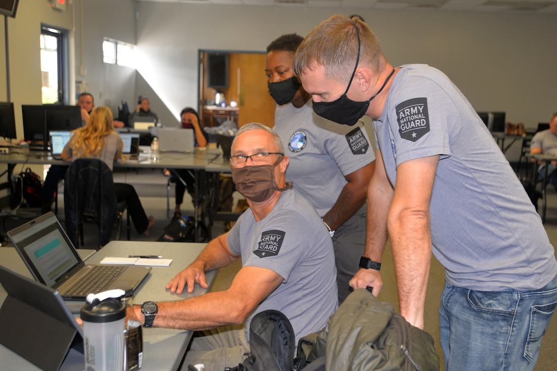 North Carolina Air National Guard (NCARNG) Chief Master Sgt. Randy Conner, left, NCARNG Staff Sgt. Latrica Quander-Freeman and North Carolina Army National Guard Staff Sgt. Todd Webster discuss cyber operations during Cyber Shield 2020 held at the North Carolina National Guard's (NCNG) Fort Fisher Training Center, Kure Beach, North Carolina, Sept. 24, 2020.  Cyber Shield 2020 is a virtual national exercise where NCNG participants join their National Guard peers across the country, testing their response to real world cyber threats to government and private industry networks and information technology infrastructure. (U.S. Army National Guard photo by Robert Jordan, North Carolina National Guard Public Affairs)