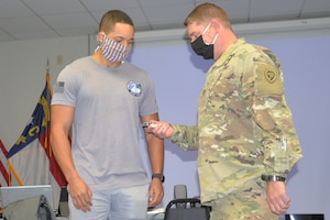 North Carolina National Guard (NCNG) Adjutant General Maj. Gen. Maj. Gen. Todd Hunt, right, gives a command coin to North Carolina Army National Guard Sgt. Michael Gibbs during Cyber Shield 2020 held at the NCNG's Fort Fisher Training Center, Kure Beach, North Carolina, Sept. 24, 2020.  Cyber Shield 2020 is a virtual national exercise where NCNG participants join their National Guard peers across the country, testing their response to real world cyber threats to government and private industry networks and information technology infrastructure. Erik A. Hooks, secretary of the North Carolina Department of Public Safety, seated far left, also met with the NCNG and North Carolina state government participants  (U.S. Army National Guard photo by Robert Jordan, North Carolina National Guard Public Affairs)