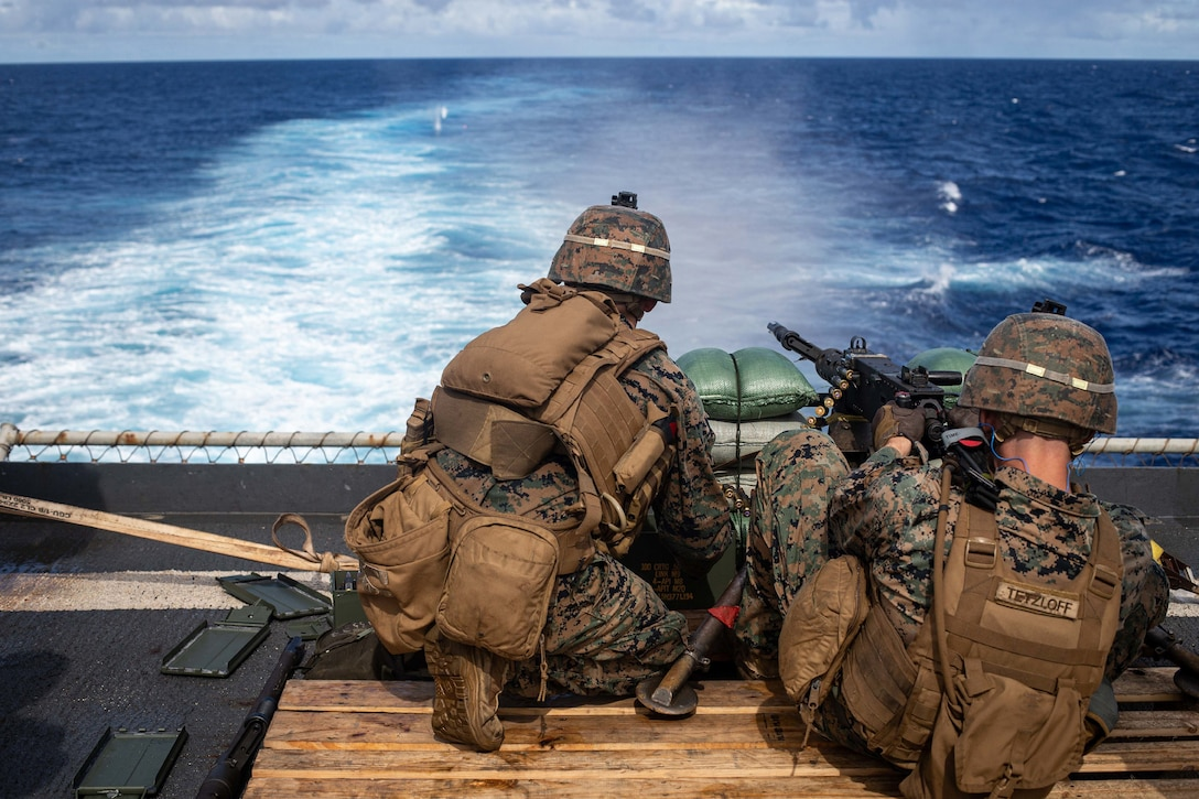 Two Marines operate a machine gun, firing out to sea.