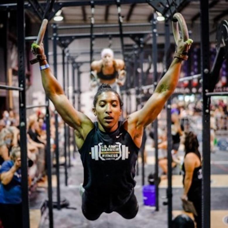 woman swings from gymnastic rings.